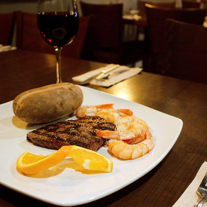 Steak with orange, shrimps and potatoes