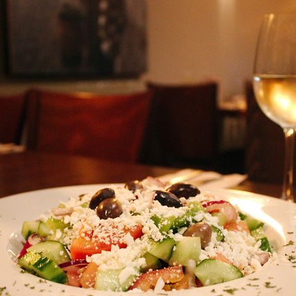 Greek salad with two glasses of white wine